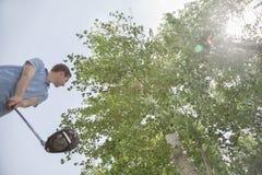 Punto di vista di angolo basso del giovane che si prepara per colpire la palla da golf sul campo da golf, chiarore della lente Fotografie Stock