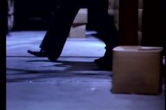 Punto di vista di angolo basso dell'uomo che insegue sospetto in magazzino video d archivio