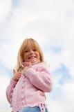 Punto di vista di angolo basso della bambina, pollici in su Immagine Stock
