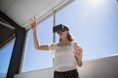 Punto di vista di angolo basso della donna di affari che per mezzo del simulatore di realtà virtuale dalla finestra Immagine Stock