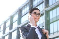 Punto di vista di angolo basso della donna di affari che per mezzo del telefono cellulare fuori dell'edificio per uffici Fotografia Stock Libera da Diritti