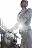 Punto di vista di angolo basso della donna di affari che sta con la bicicletta il giorno soleggiato Immagini Stock Libere da Diritti