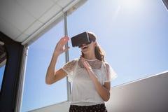 Punto di vista di angolo basso della donna di affari felice che per mezzo del simulatore di realtà virtuale Immagini Stock Libere da Diritti