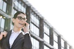 Punto di vista di angolo basso della donna di affari felice che per mezzo del telefono cellulare fuori dell'edificio per uffici Immagine Stock