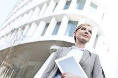Punto di vista di angolo basso della donna di affari sicura che tiene compressa digitale fuori dell'edificio per uffici Fotografia Stock Libera da Diritti
