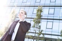 Punto di vista di angolo basso della donna di affari sorridente che per mezzo del telefono cellulare il giorno soleggiato Immagine Stock