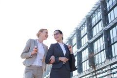 Punto di vista di angolo basso delle donne di affari felici che camminano fuori dell'edificio per uffici contro il chiaro cielo Immagini Stock