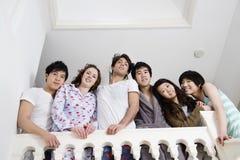 Punto di vista di angolo basso di giovani amici che sorridono insieme Immagini Stock Libere da Diritti