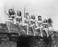 Punto di vista di angolo basso di un gruppo di donne che si siedono su una struttura di pietra e che ondeggiano le loro mani (tut Fotografia Stock