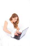 Punto di vista di angolo della donna che per mezzo del computer portatile a letto Fotografia Stock Libera da Diritti