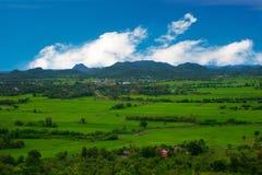 Punto di vista di paese con la montagna dietro in cielo blu Fotografia Stock