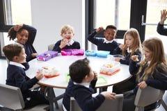 Punto di vista elevato dei bambini della scuola primaria che si siedono insieme ad una tavola rotonda che mangia i loro pranzi im fotografia stock