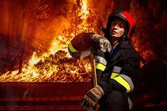 Punto di vista frontale di un pompiere nell'azione per estinguere la fiamma in foresta immagini stock