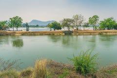 Punto di vista di gestione delle acque nelle risaie dal canale di irrigazione prima della piantatura immagini stock
