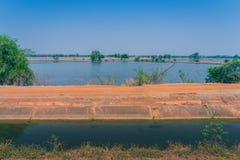 Punto di vista di gestione delle acque nelle risaie dal canale di irrigazione prima della piantatura fotografie stock