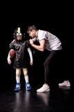 Punto di vista integrale dell'allenatore che istruisce il giocatore di football americano del ragazzo Fotografia Stock
