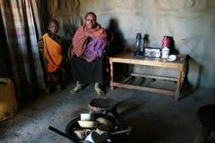 Punto di vista interno della capanna, della donna di colore e dei bambini di maasai all'interno Fotografie Stock