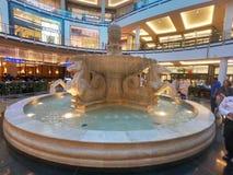 Punto di vista interno della gente che cammina intorno alla fontana dei cavalli dentro il centro commerciale degli emirati situat fotografia stock