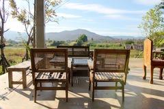 Punto di vista di legno della sedia sulle montagne e sul prato superiori fotografia stock
