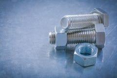 Punto di vista orizzontale dei dadi inossidabili dei bulloni su backgr metallico Immagine Stock