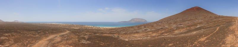 Punto di vista panoramico di Playa de las Conchas e cratere vulcanico sotto un cielo blu senza nuvole La Graciosa, Lanzarote, iso Fotografia Stock