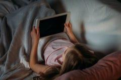 punto di vista parziale del bambino che per mezzo della compressa a letto Fotografie Stock