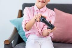 punto di vista parziale del bambino con gamepad in mani che giocano video gioco Fotografia Stock