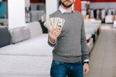 punto di vista parziale del cliente maschio che mostra le banconote del dollaro Fotografie Stock Libere da Diritti