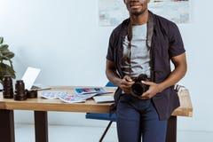 punto di vista parziale del fotografo afroamericano con la macchina fotografica della foto che si appoggia posto di lavoro Immagine Stock