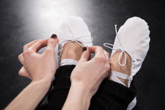 Punto di vista parziale del primo piano del ballerino della donna che lega le scarpe di balletto Immagini Stock Libere da Diritti