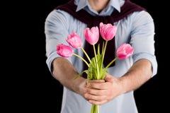Punto di vista parziale del primo piano dell'uomo che presenta i bei tulipani rosa sul nero Immagini Stock Libere da Diritti