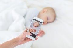 Punto di vista parziale del primo piano della madre che fotografa figlio addormentato adorabile con lo smartphone immagine stock libera da diritti