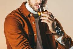 punto di vista parziale dell'uomo in abbigliamento alla moda con vetro di whiskey a disposizione Immagine Stock Libera da Diritti