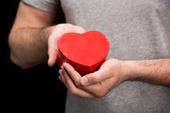 Punto di vista parziale dell'uomo che mostra cuore in mani sul nero Immagini Stock Libere da Diritti