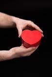 Punto di vista parziale dell'uomo che mostra cuore in mani sul nero Fotografia Stock