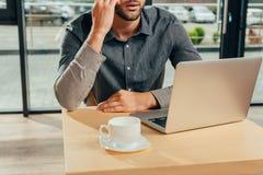punto di vista parziale dell'uomo che si siede alla tavola con il computer portatile e la tazza di caffè Fotografia Stock