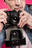 Punto di vista parziale dell'uomo che tiene la retro macchina fotografica della foto in mani Immagini Stock