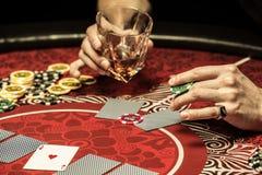 Punto di vista parziale dell'uomo che tiene vetro del chip di mazza e del whiskey alla tavola Immagine Stock Libera da Diritti