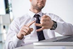 Punto di vista parziale dell'uomo d'affari che conta sulle dita nel luogo di lavoro Fotografie Stock