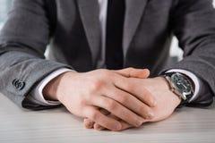 Punto di vista parziale dell'uomo d'affari con le mani in serratura che si siede alla tavola Fotografia Stock Libera da Diritti