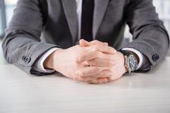 Punto di vista parziale dell'uomo d'affari con le mani in serratura che si siede alla tavola Immagini Stock