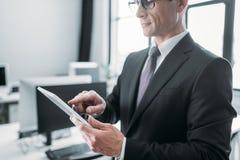 punto di vista parziale dell'uomo d'affari facendo uso della compressa Fotografia Stock