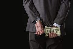 Punto di vista parziale dell'uomo d'affari in manette che tengono soldi sul nero Fotografie Stock