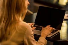 punto di vista parziale della donna di affari che per mezzo del computer portatile con lo schermo in bianco Fotografia Stock