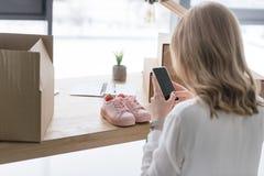 punto di vista parziale della donna di affari che prende immagine del prodotto sullo smartphone Immagini Stock