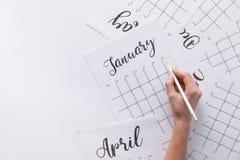 punto di vista parziale della donna che fa le note in calendario Immagine Stock Libera da Diritti
