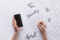 punto di vista parziale della donna con lo smartphone a disposizione che fa le note in calendario Fotografia Stock Libera da Diritti