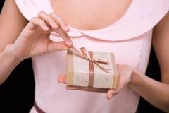 Punto di vista parziale della donna in contenitore di regalo rosa della tenuta del vestito sul nero Immagine Stock