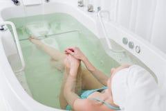 punto di vista parziale della donna in vestito di nuoto con l'asciugamano sulla testa che si rilassa nel bagno Immagini Stock