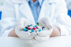 Punto di vista parziale dello scienziato in guanti protettivi che tengono le pillole in mani Fotografia Stock Libera da Diritti